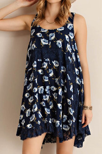 Floral print sleeveless handkerchief hem dress featuring lace detailing throughout and on bottom hem.