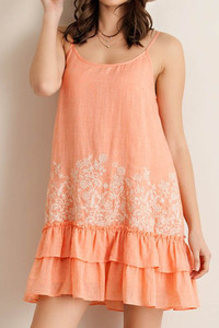 Solid ruffled shift dress featuring floral detailing.