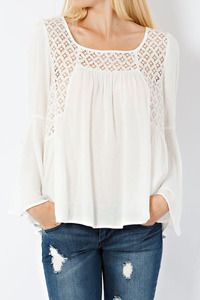 peasant top featuring ikat pattern lace on yoke. Bell sleeves. Slightly open bac