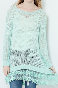 A solid sweater tunic top featuring edge lace on bottom